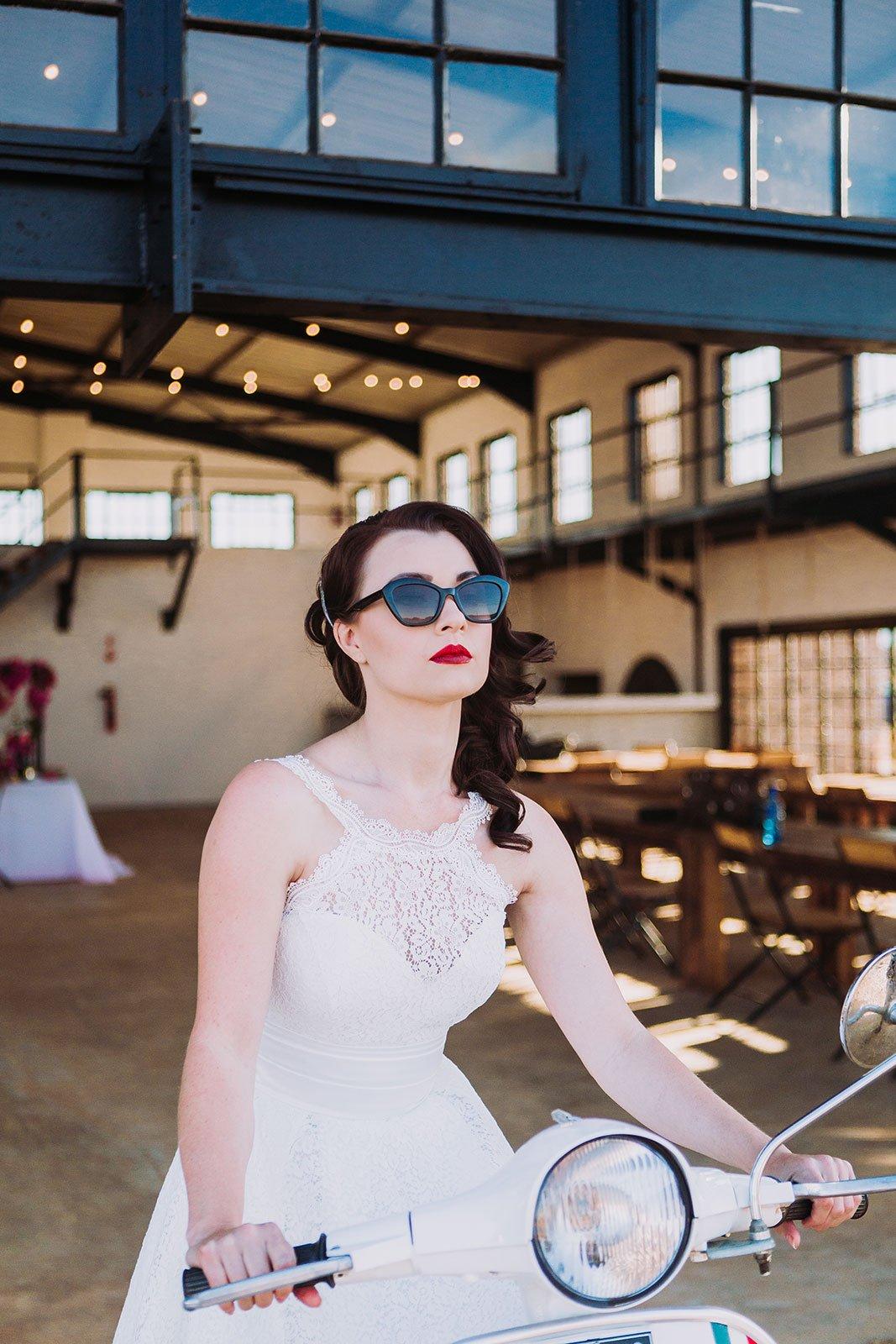 Bride arriving at wedding in The Nut Farm in Vespa